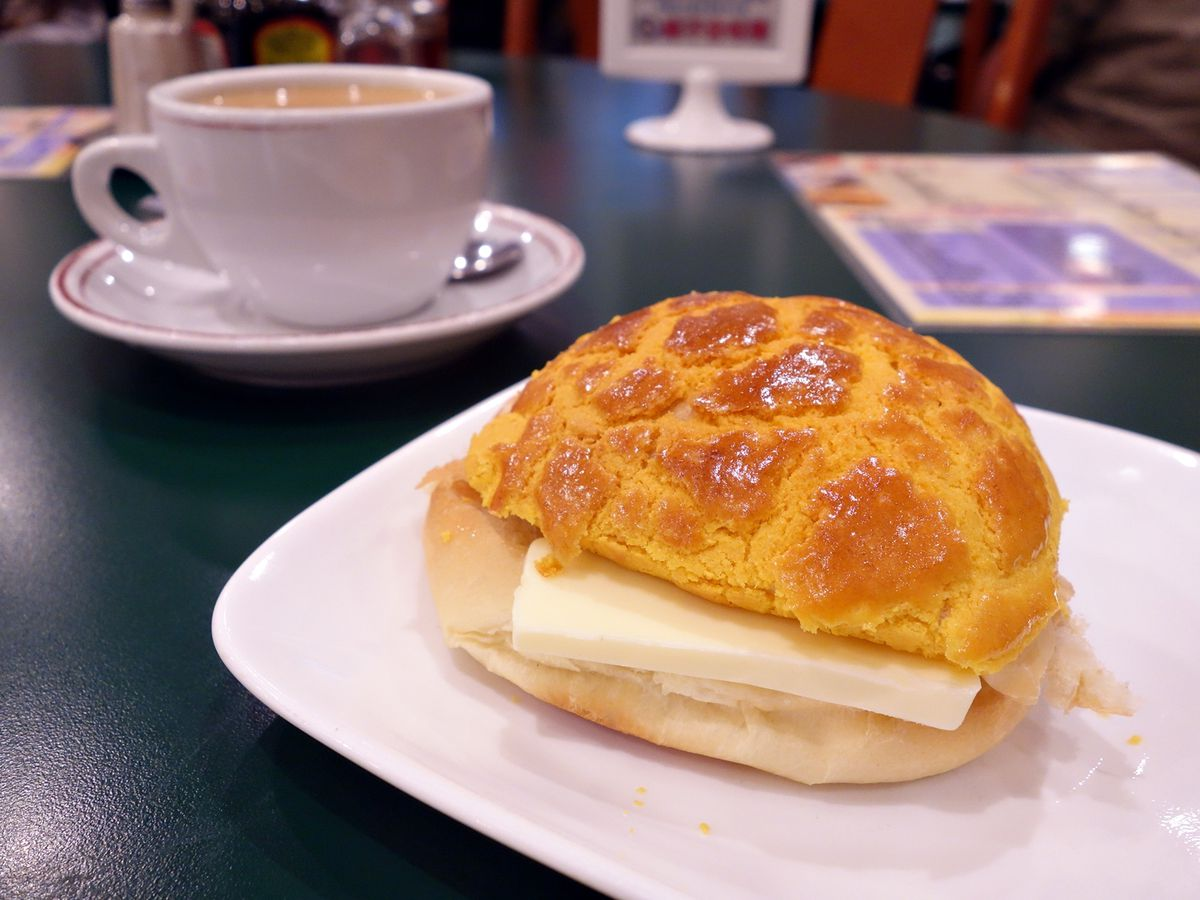 A pastry, patterned from rising in the oven and glossy on the crust, sits split open with a large wedge of butter in the middle on a small plate near a cup of coffee and a menu, blurred in the background, on a formica tabletop.