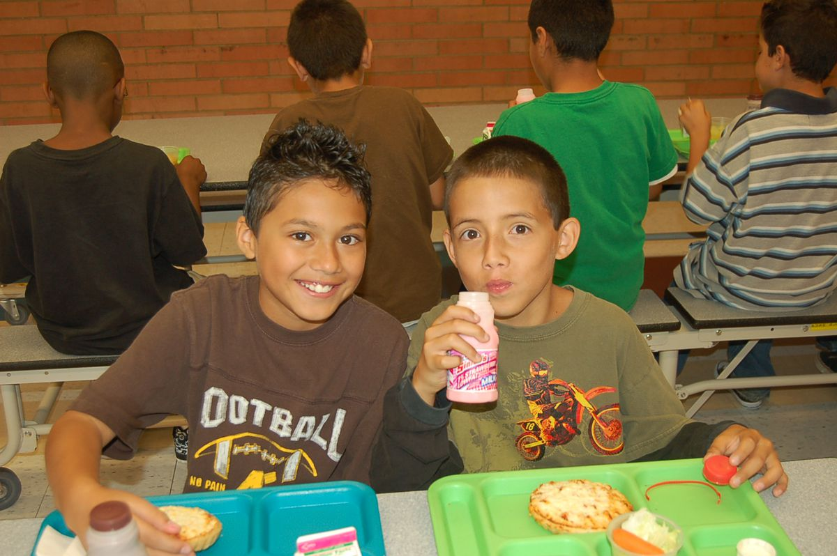 """Some students at Aurora's Park Lane Elementary eat lunch. The cafeteria pizza - unlike most pizzas - is made with whole wheat and lowfat cheese, so it's a """"Slow"""" food. The lowfat milk is a """"go"""" food."""
