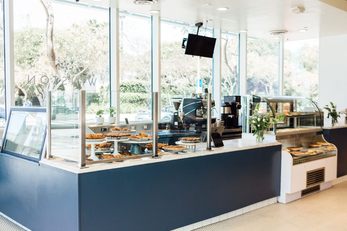 A light and airy pie shop with blue tones and glass between customer and worker.