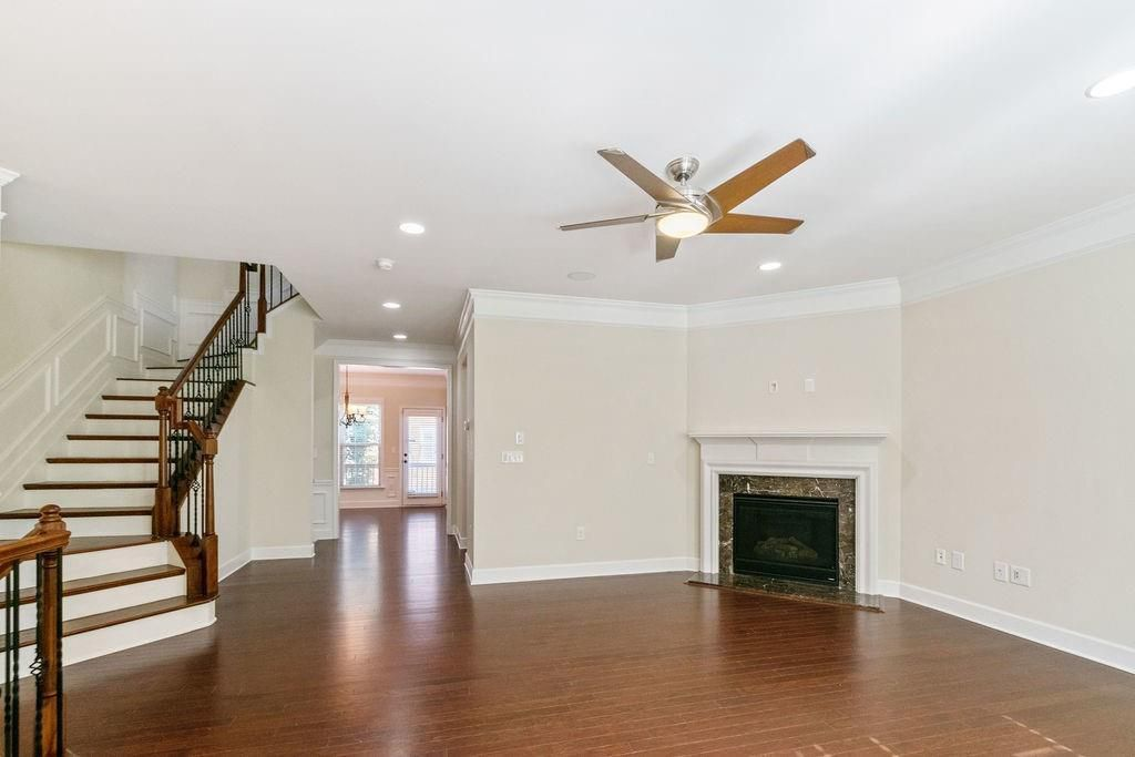Empty living room with fireplace, ceiling fan and light, and stairs on the left leading upstairs.