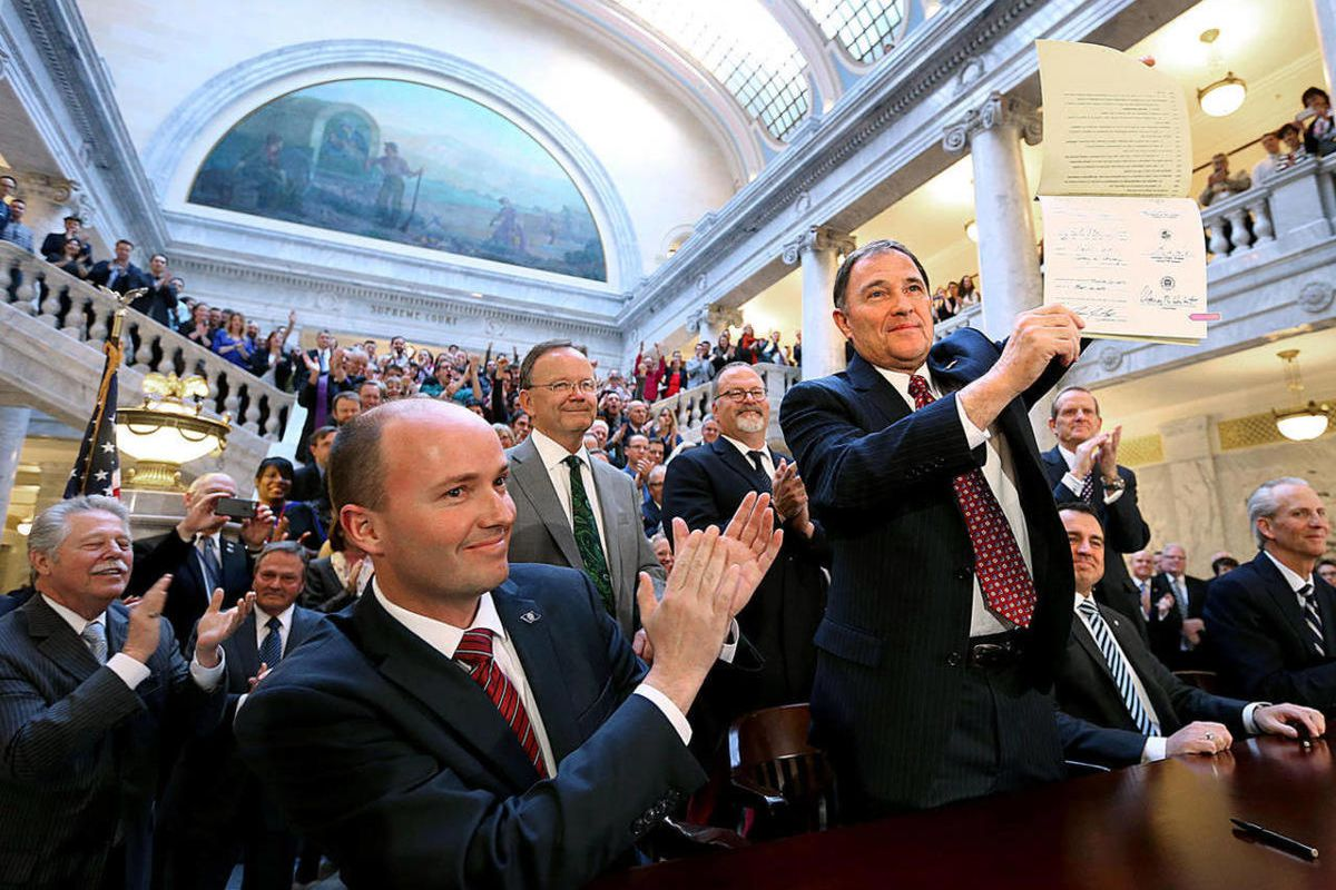 FILE - Gov. Gary Herbert holds up a copy of SB296 after signing it at the Capitol in Salt Lake City, Utah, on Thursday, March 12, 2015.  Herbert signed 33 bills on Monday, including a measure phasing out a tax credit for installing solar panels that legis