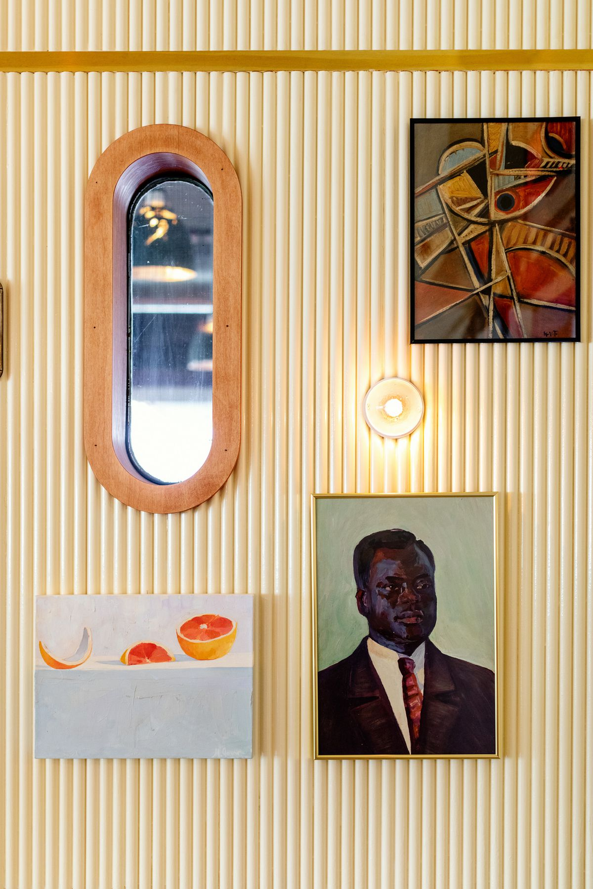 Three art pieces and a mirror on the wall of the dining room