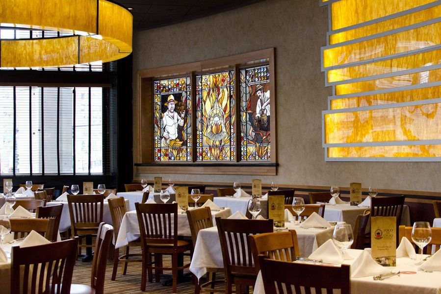 An interior shot of Fogo de Chao in Boston, with stained glass, white tablecoth-covered tables, and yellow accents