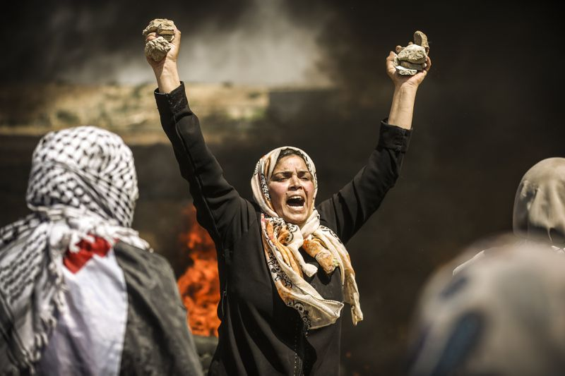 A Palestinian woman holds stones and shouts slogans as she takes part in the protest.