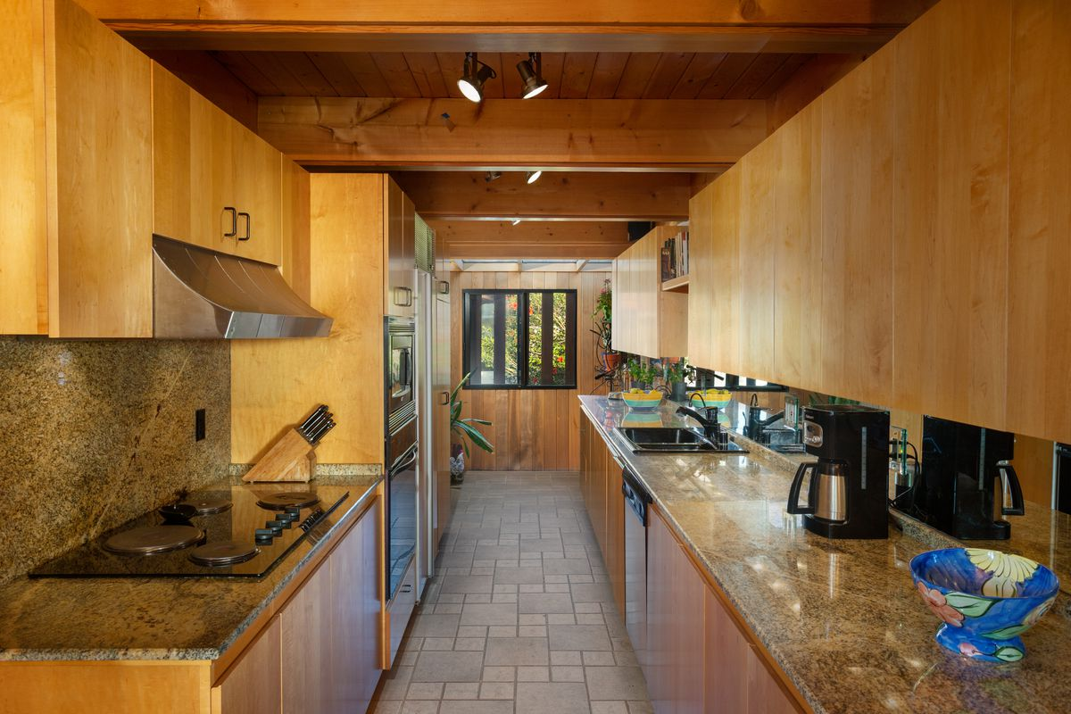 A kitchen with wooden cabinets and tiled floors.