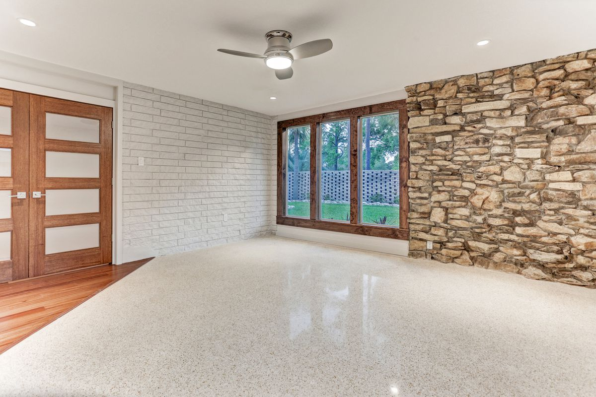 An empty room that works as an office or as a bedroom has terrazzo floors and a tripanel window.