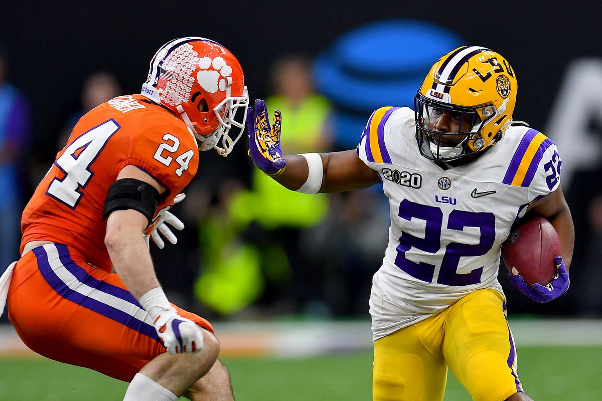 Clyde Edwards-Helaire #22 of the LSU Tigers gives Nolan Turner #24 of the Clemson Tigers a stiff arm during the fourth quarter of the College Football Playoff National Championship game at the Mercedes Benz Superdome on January 13, 2020 in New Orleans, Louisiana. The LSU Tigers topped the Clemson Tigers, 42-25.