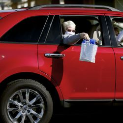 Ann Bell's friends drive by with gifts after her wedding to Enoch Bell in Kaysville on Friday, April 24, 2020.