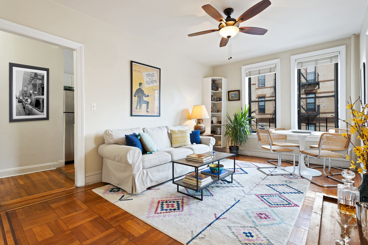 The living room has parquet wood floors and two windows that look towards other buildings.