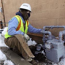 Joey Stephenson, a Dominion Energy utility worker, paints a gas meter and surrounding pipes after the meter was replaced for quality control in West Valley City on Wednesday, Feb. 17, 2021.