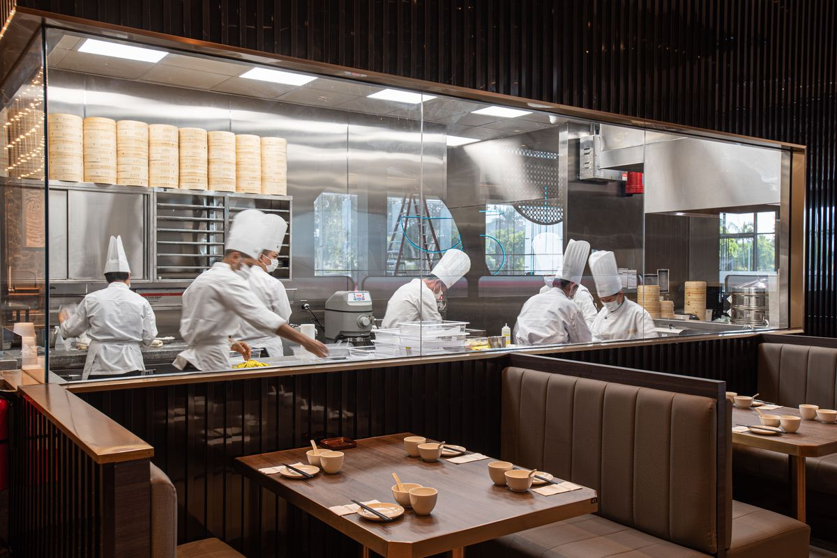 Workers in white coats and chefs hats make dumplings behind glass.