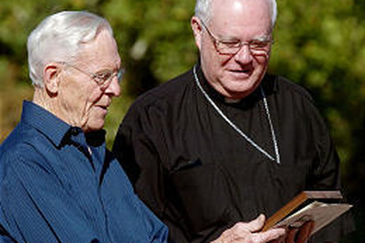 Bishop George H. Niederauer, right, receives an award from Boyer Jarvis of the Gandhi Alliance for Peace on Sunday at Jordan Park.