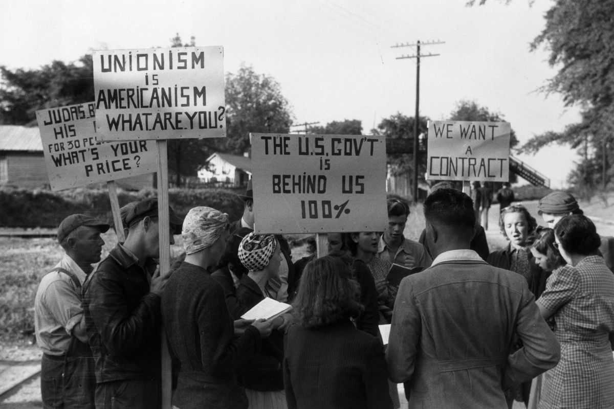 A group people stand together holding signs