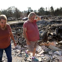 Sisters Misty Pantle and Tammy Johnson get their first look at the burned remnants of the home they shared with Pantle's three teenage children in Talent, Ore., on Saturday, Sept. 19, 2020. Their home was one of more than 2,300 residences destroyed when the Almeda Fire swept through the towns of Talent and Phoenix in southern Oregon.