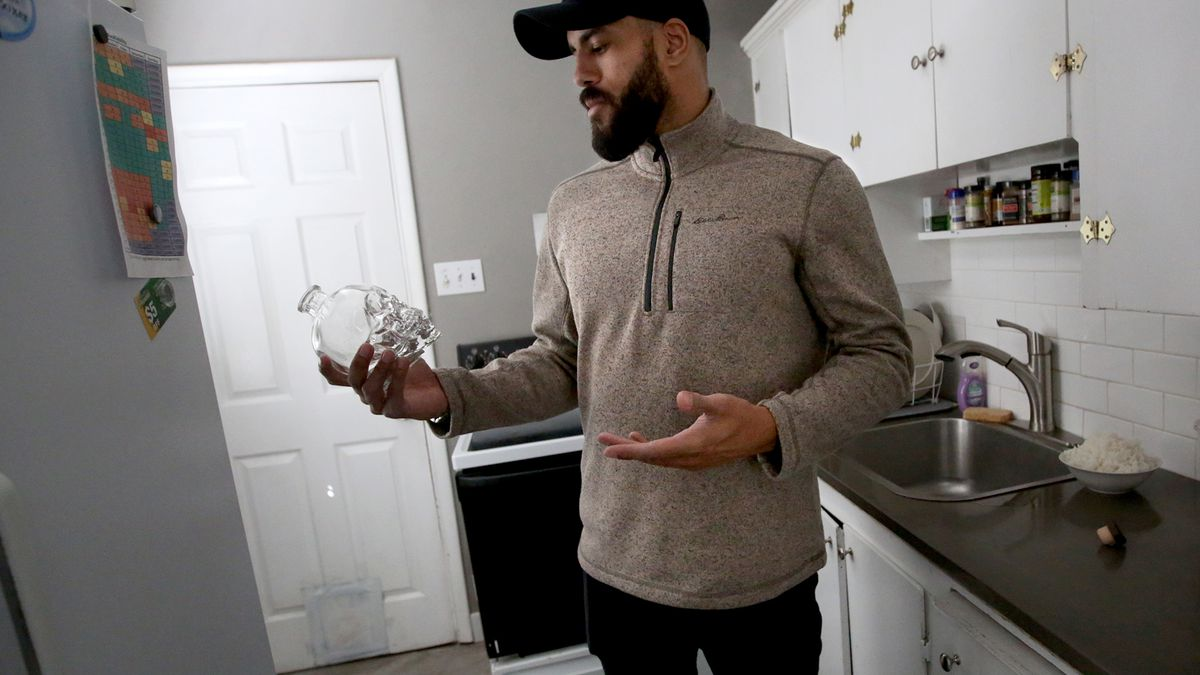 Christian Tyler holds a bottle that belonged to his best friend and cousin, who was shot to death, at his home in Salt Lake City on Monday, March 26, 2018.