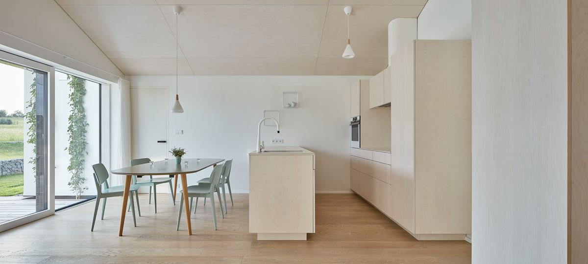 A modern, minimalist kitchen with pale wood cabinetry, white walls, a dining room set for four, and large windows.