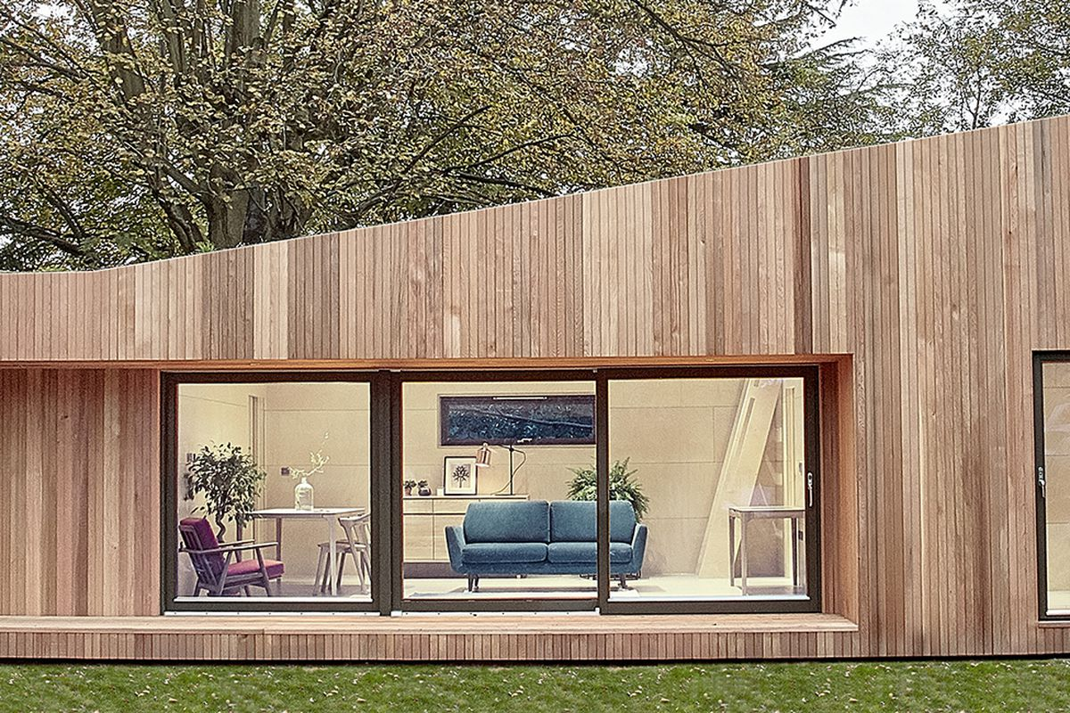 Exterior shot of small wood-clad prefab house with large sliding glass doors and an asymmetrical roof.