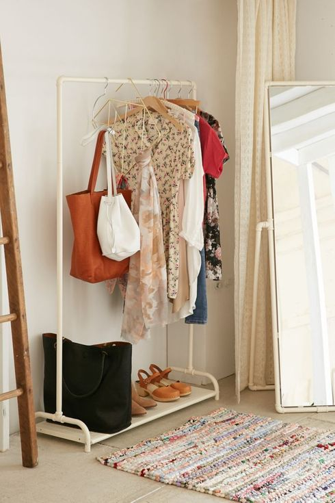 Cream clothing rack with dresses hanging on it.