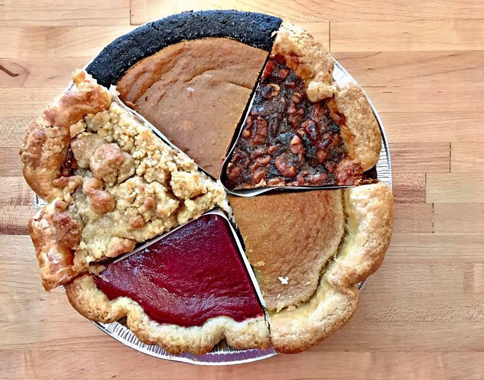 From above, a full pie made up of slices from five different pies topped with various crusts and crumbles