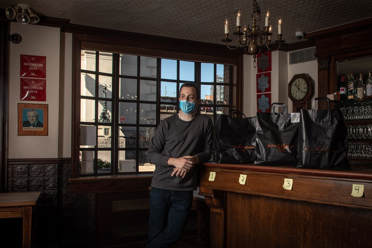 David Berson stands in the bar area of Peter Luger next to takeout bags