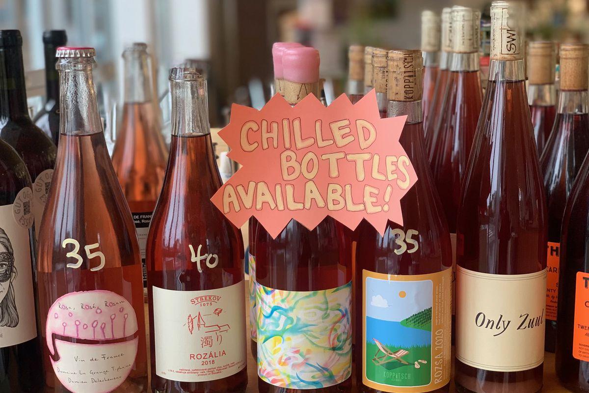 """贴在一组红色和粉色葡萄酒瓶子上的一个牌子上写着:""""冰瓶有售!"""""""