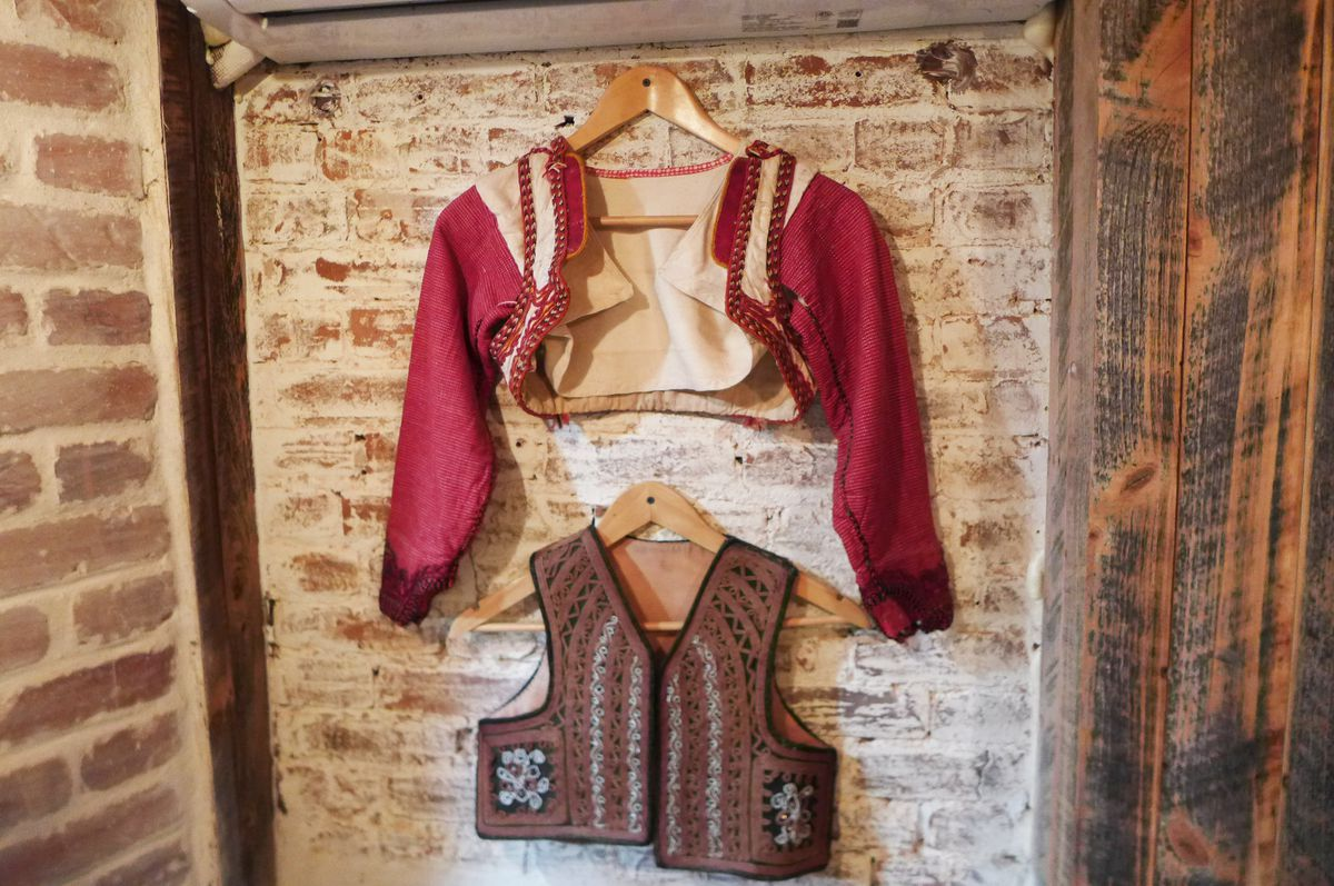 Two red and brown short blouses or maybe they're jackets, dancing costumes from Kosovo's past.