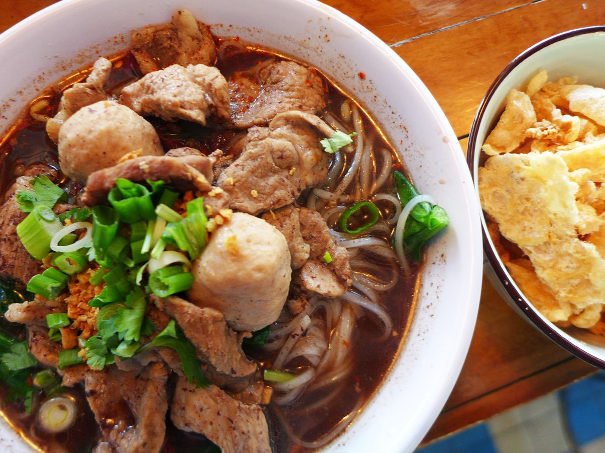 A bowl of dark broth is jammed with pork and pork balls, with a bowl of crunchy pig skin on the side.