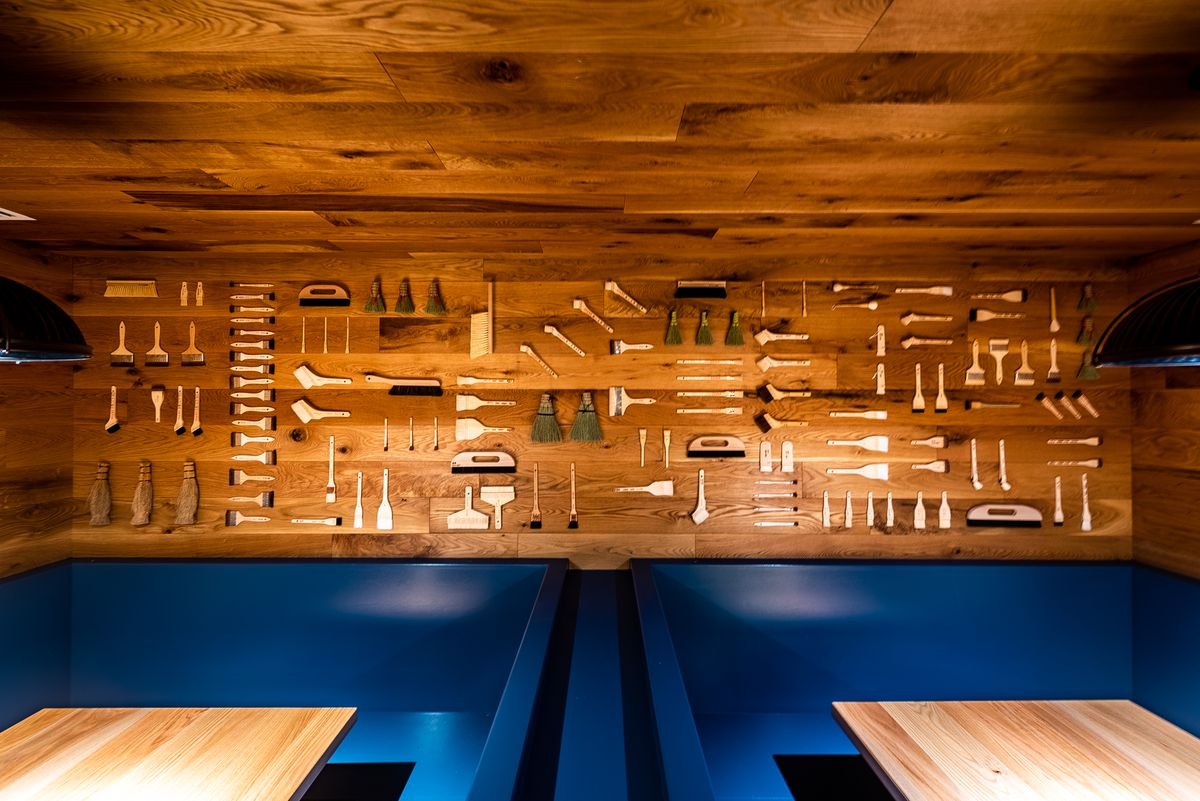 Japanese brushes line the wall above booths reminiscent of shipping containers at Hatoba