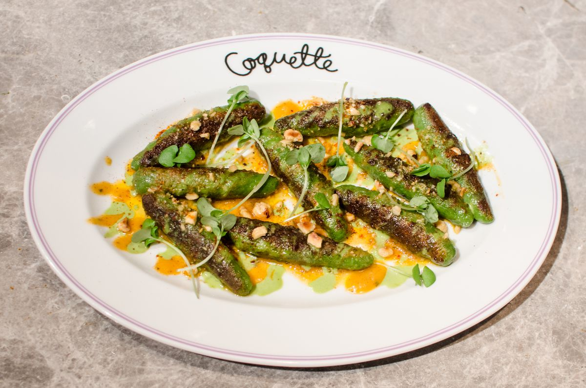 Browned French-style spinach gnocchi —long green tubes —sit on an oval plate with Coquette written in cursive on it.