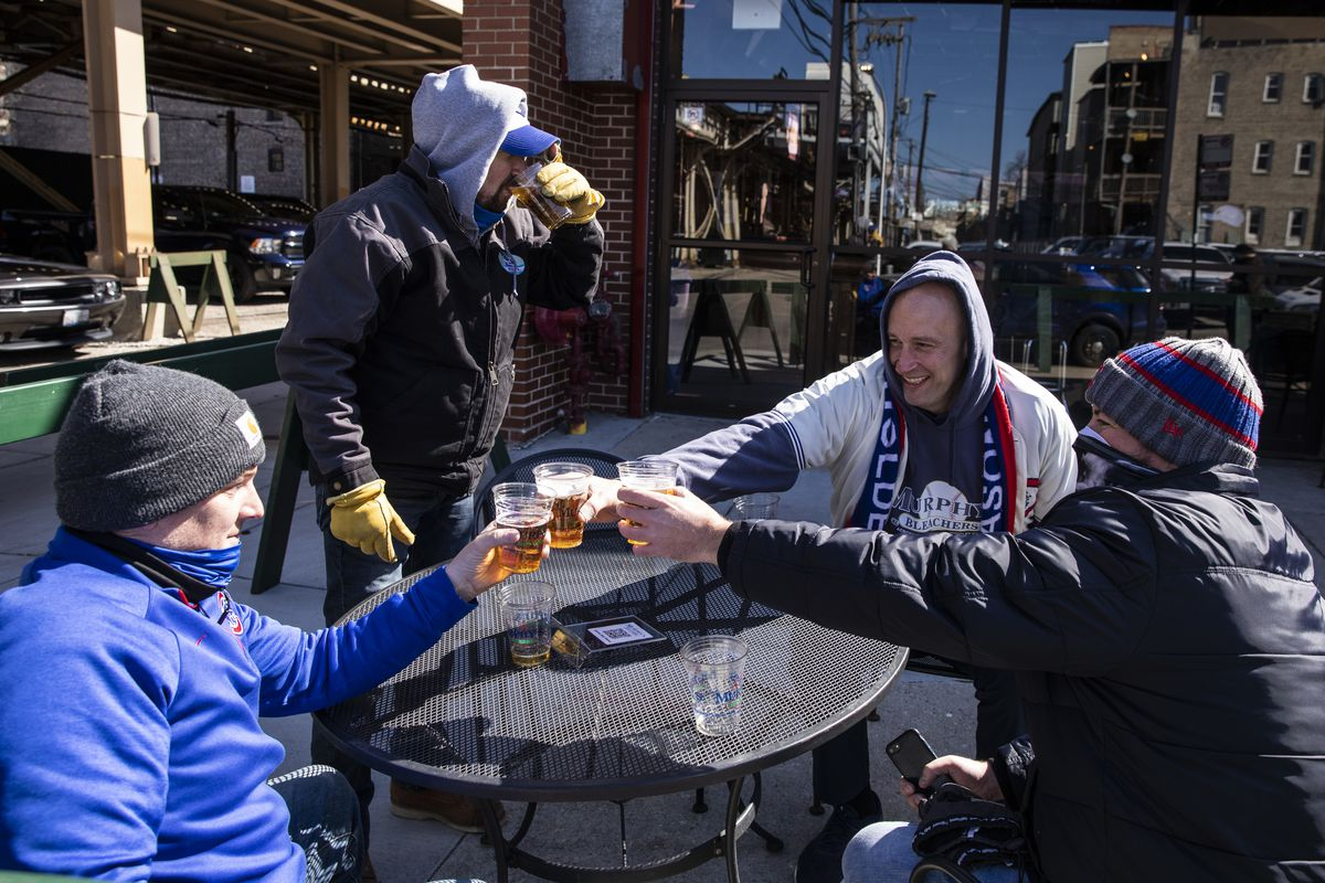 Damian Ehrlicher (center right, in grey), of Edison Park, drinks with friends at Murphy's Bleachers during the Chicago Cubs Opening Day game against the Pittsburgh Pirates.