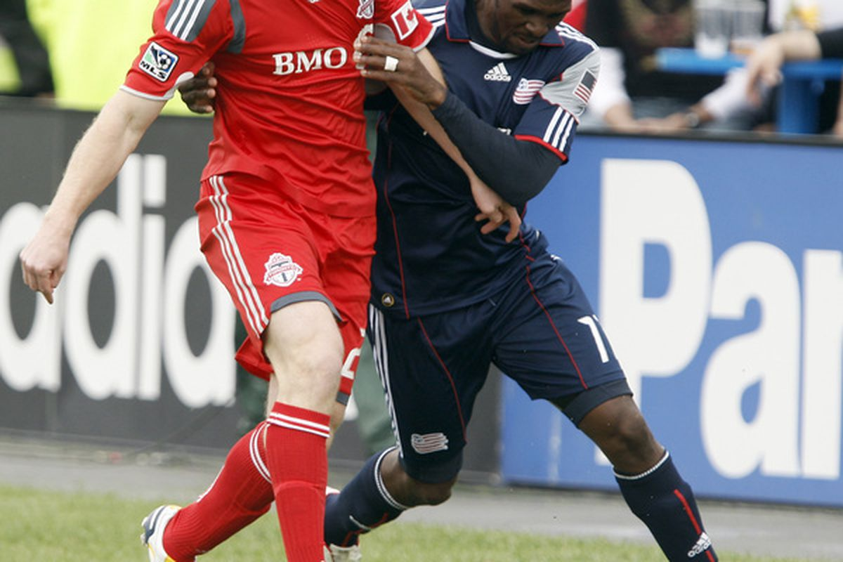 TORONTO - MAY 22: Jacob Peterson #23 of Toronto FC battles for the ball with Kheli Dube #11 of the New England Revolution during a MLS game at BMO Field May 22, 2010 in Toronto, Ontario, Canada. (Photo by Abelimages/Getty Images)