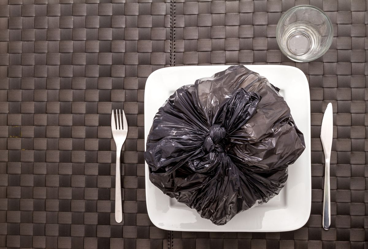 A table setting with a full garbage bag on the plate.