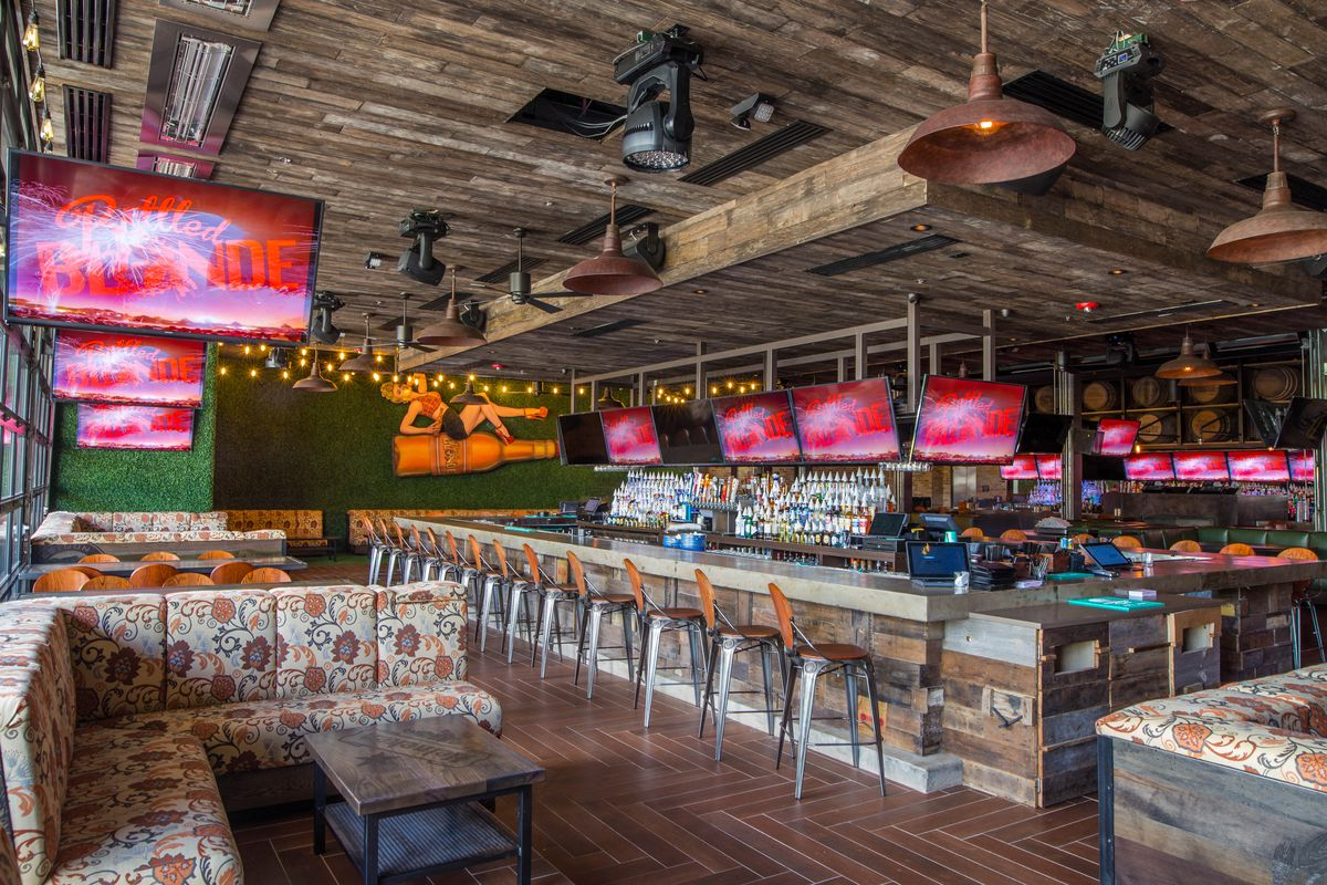 The interior of Bottled Blonde in Houston. Floral patterned banquettes sit on a herringbone pattern wood floor with a rustic wood bar and TV screens in the background.