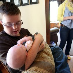 Jack Simmons holds his baby nephew James at home in Kamas on Saturday, Aug. 24, 2013. Jack was adopted.