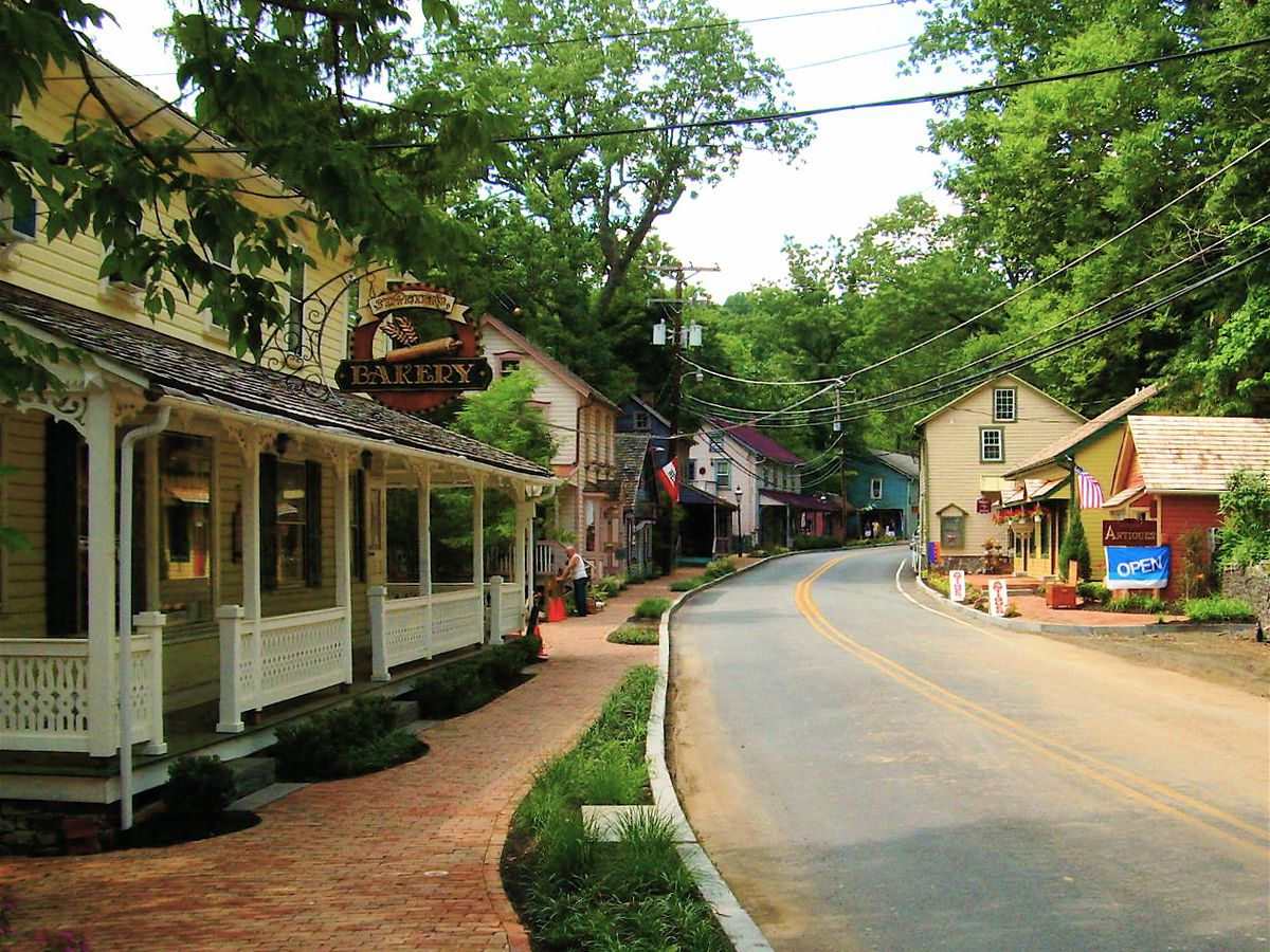 A street in the town of St. Peter's Village, Pennsylvania. The street is lined with shops, houses, and trees.