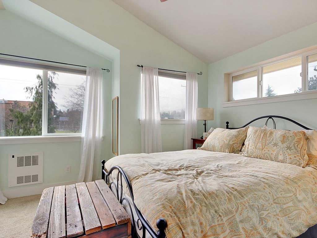 A bedroom with a large bed and a wood trunk at the foot, and vaulted ceilings.