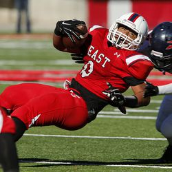 Jaylen Warren of East stretches for yardage against Brennen Rymer of Springville during 4A semifinal high school football in Salt Lake City, Thursday, Nov. 12, 2015.