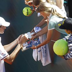 U.S. players John Isner signs autographs after winning his match against French player Jo-Wilfried Tsonga, in the quarterfinal of the Davis Cup between France and U.S. in Monaco, Sunday April 8, 2012.  The U.S. team qualifies for the semi-final.(AP Photo/Remy de la Mauviniere)