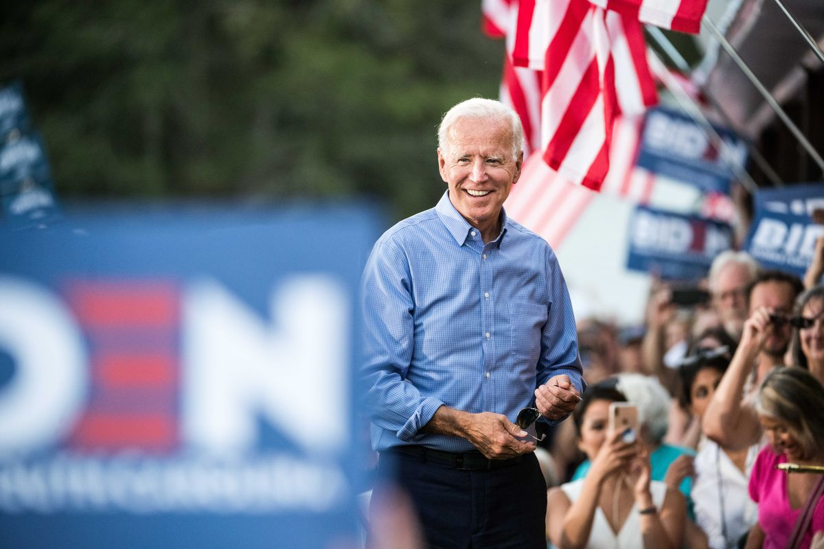 Biden smiles beneath US flags as a crowd behind him cheers, holding Biden for president signs.