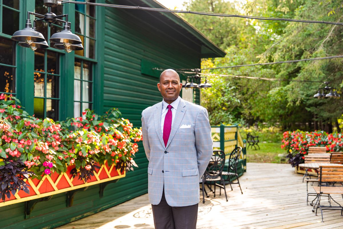 Dillard, who is black and bald, stands on a restaurant patio in his jacket and tie.