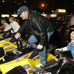 BYU head football coach Bronco Mendenhall races his sons Raeder (far right), Cutter (to left of Brono) and Breaker (far left) in a wave runner arcade game at the ESPN Zone. BYU players, coaches and families were hosted at the ESPN Zone Welcome Reception at the New York New York Hotel in Las Vegas.