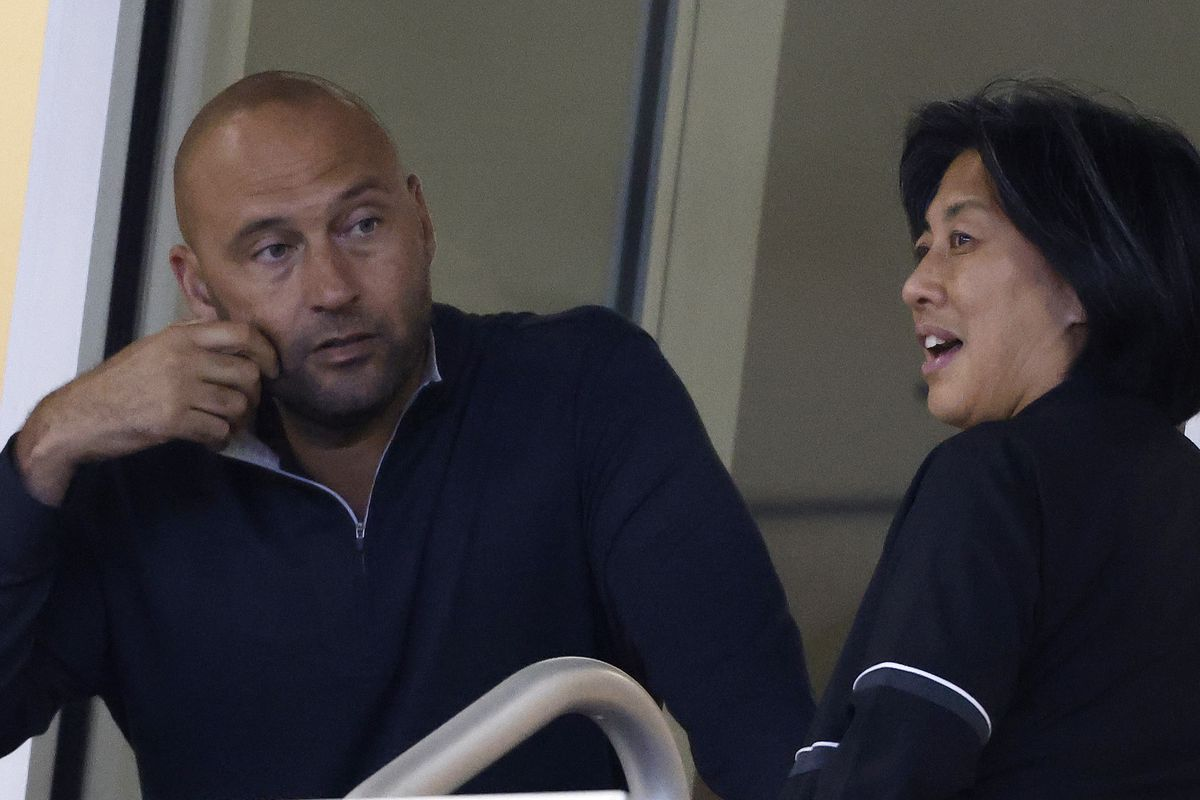CEO Derek Jeter of the Miami Marlins talks with general manager Kim Ng during the seventh inning against the New York Mets at loanDepot park