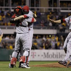 Cincinnati Reds starting pitcher Homer Bailey hugs Cincinnati Reds catcher Ryan Hanigan, center, as first baseman Joey Votto (19) and third baseman Scott Rolen, left join the celebration after getting the final out of a no-hitter in a baseball game against the Pittsburgh Pirates in Pittsburgh Friday, Sept. 28, 2012. The Reds won 1-0.