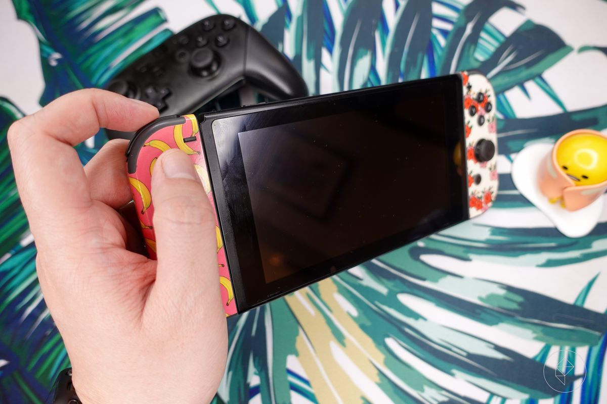 A person holding a Nintendo Switch awkwardly