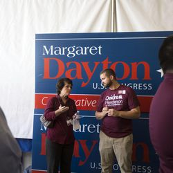 A Deidre Henderson supporter stands in front of a Margaret Dayton campaign poster to talk about her plans and ideas while campaigning for the vote of Republican delegates at Timpview High School in Provo on Saturday, June 17, 2017.
