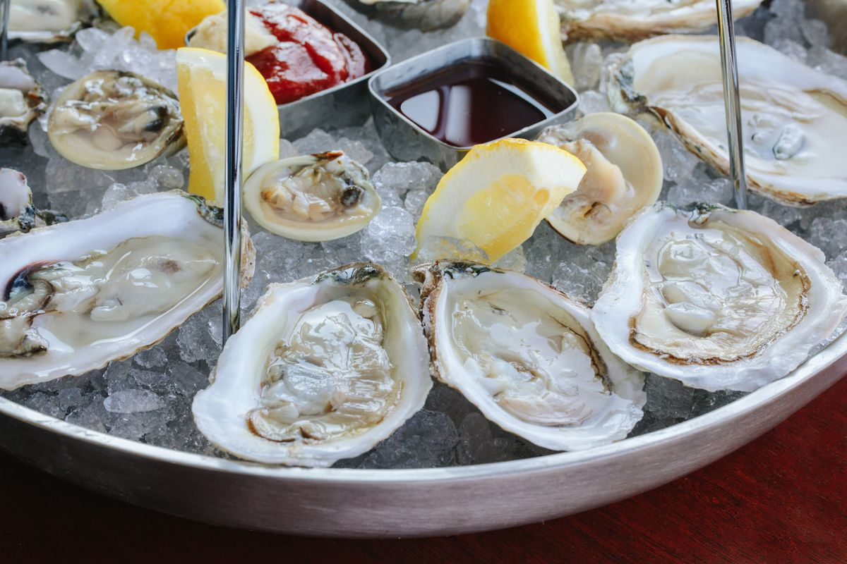 A plate of oysters on the half shell from Reelhouse oyster bar. The oysters are accompanied by mignonette, cocktail sauce, and lemon wedges.