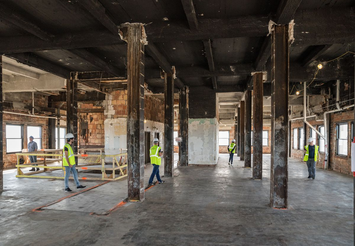 A large, open space.  Steel beams evenly distributed over a concrete floor with lots of exposed bricks.