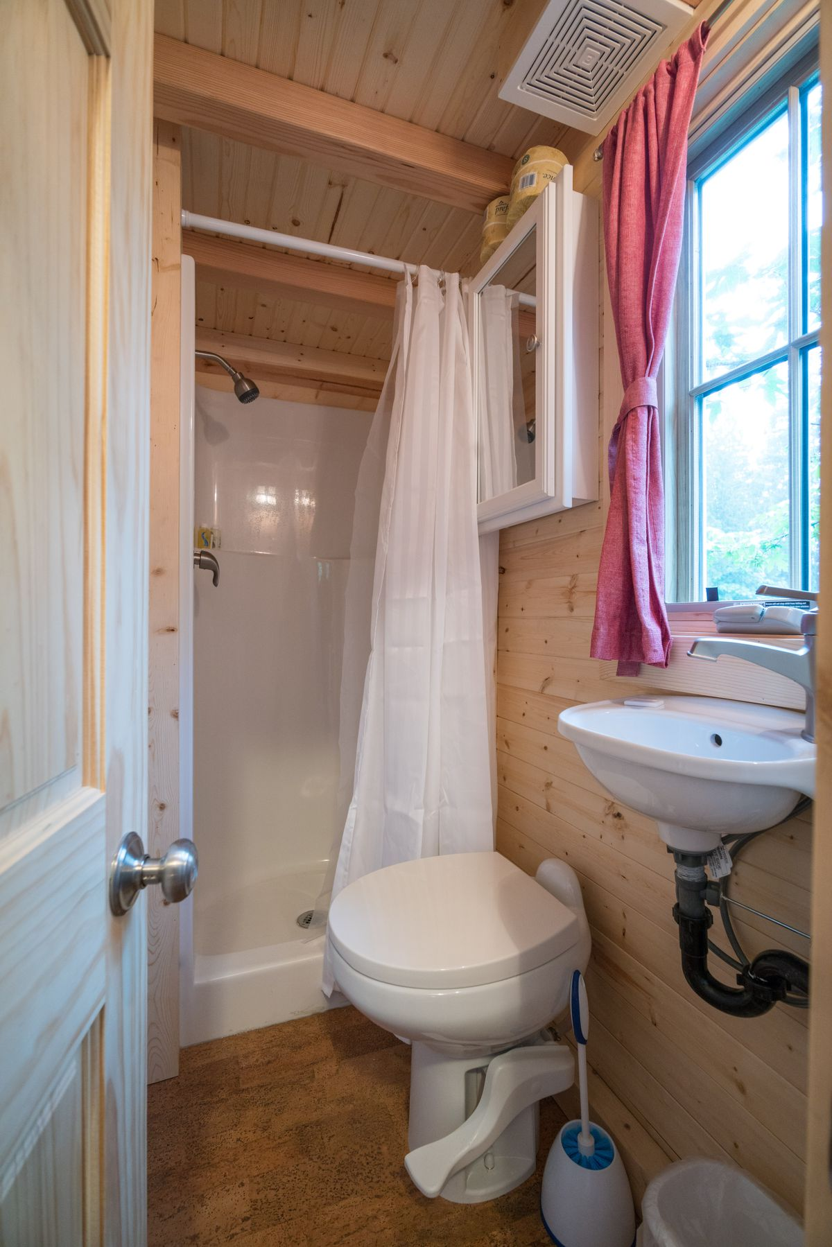 A shower, toilet, and micro sink in a tiny home.