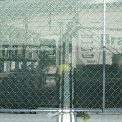 1:03 p.m. View through a gap in the fence, obstructed by more fences, in front of the ballpark -
