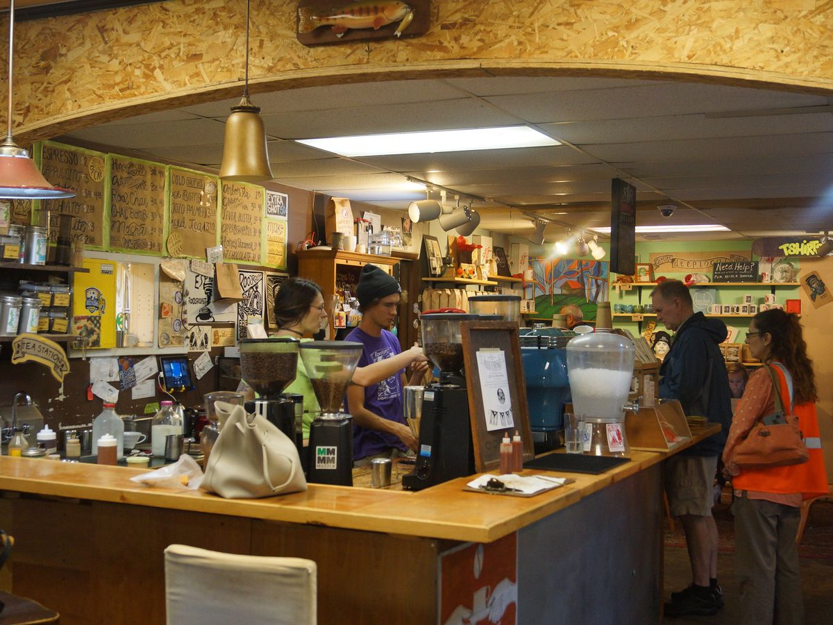 Barista's stand behind a wooden bar surrounded by plywood walls and brown paper menu boards as customers place orders.